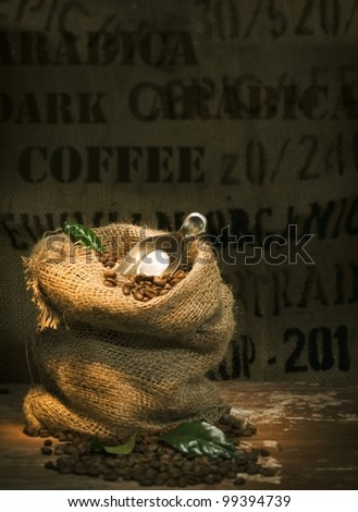 Small rustic hessian bag filled to overflowing with fresh roasted coffee beans and topped with a small trowel and green leaves on a dark background with copyspace - stock photo