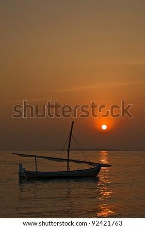 Small sail boat on a sunset, Maldives - stock photo