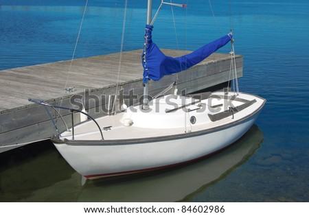 Small Sailboat:  A small white boat waits at a wooden dock. - stock photo