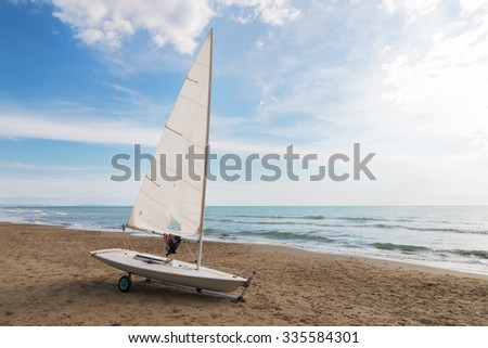 small sailboat on a cart at the beach ready to sailing. life jacket hanging from the boom - stock photo