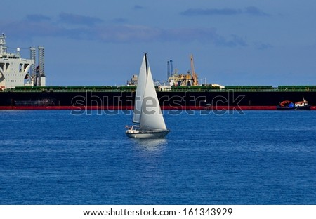Small sailboat sailing on the bay and next to large supertanker docked - stock photo