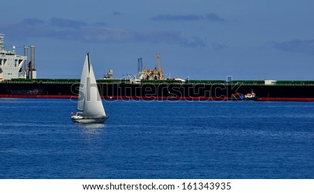 Small sailboat sailing on the calm sea and next to a large tanker docked - stock photo