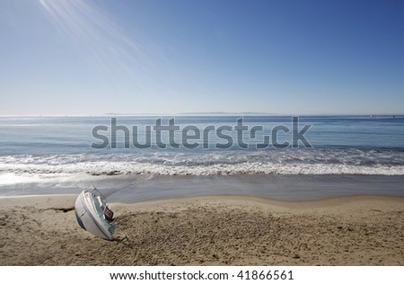 Small sailboat washed up on shore.