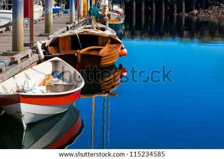 Small sailboats tied at the dock with reflections with copy space