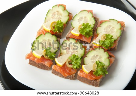 small salmon sandwich on plate over white - stock photo