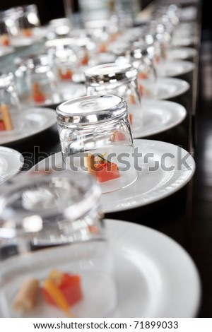 Small salmon snacks covered with glasses, selective focus - stock photo