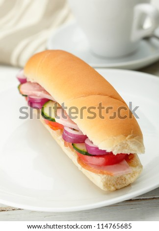 Small sandwich with deli meats and vegetables on a white plate