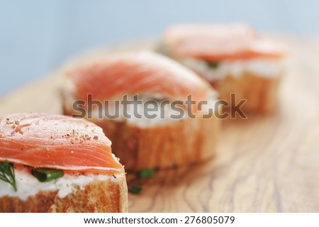 small sandwiches with soft cheese and salmon on wood table - stock photo