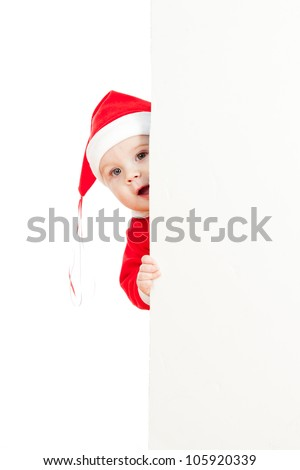 small Santa claus child looking from behind the placard - stock photo
