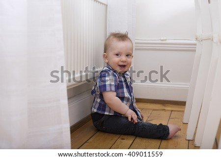 small scandinavian blond cute boy toddler playing, smiling and sitting behind the chairs - stock photo
