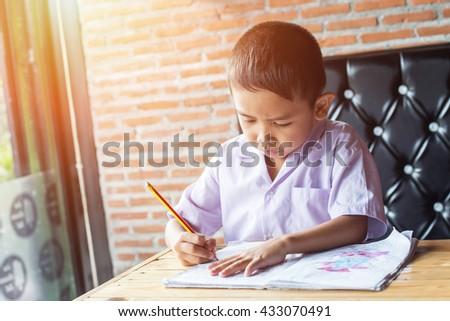 small school boy writing homework from school in workbook - stock photo