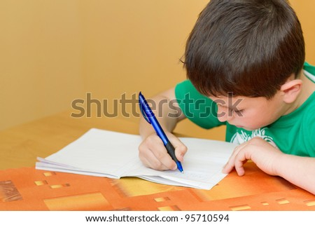 small school boy writing homework from school in workbook - stock photo