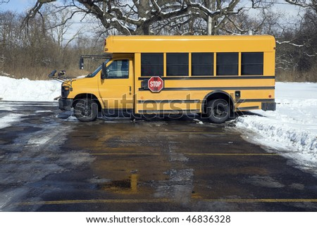 Small school bus on the parking lot - winter time. - stock photo