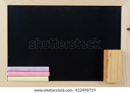 Small school wooden blank blackboard and chalks  - stock photo