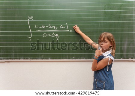 Small schoolgirl trying to solve an integral equation but it is too difficult for her so she only standing in front of the chalkboard and thinking. - stock photo