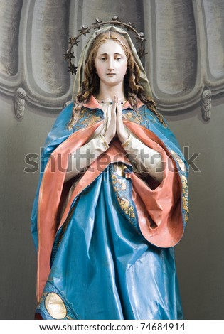 Small sculpture of Mary praying. - stock photo