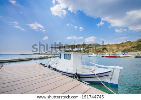 Small sea fishing boat anchored at harbor boardwalk with a nice cloudy blue sky, Marsaxlokk Harbor, Malta - stock photo