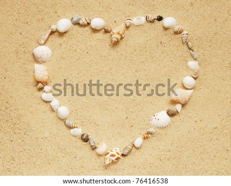 small seashells in the shape of a heart on a smooth sandy beach - stock photo