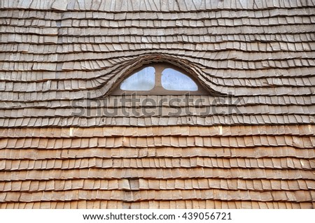 Small semicircular attic window in the roof of wooden shingles. Close up.