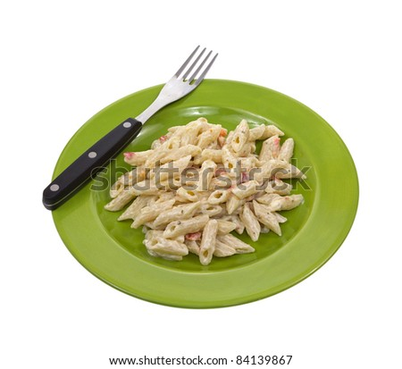 Small serving of Italian seasoned pasta on a green dish with fork on a white background. - stock photo