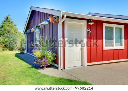 Small shed with red and purple and bird houses.
