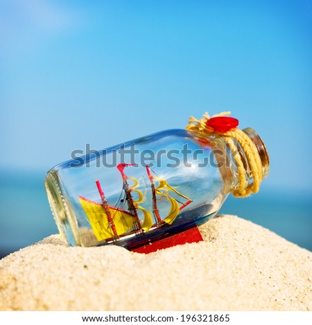 Small ship in the glass bottle, on top of the sand pile. - stock photo
