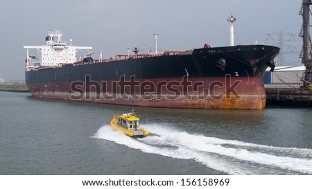 Small ship passing a big ship - stock photo