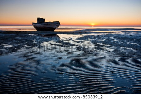 Small shipwreck stranded on the beach at sunset