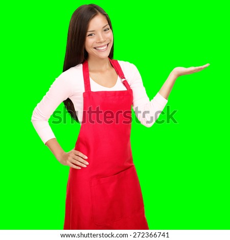 Small shop owner showing empty copy space in red apron. Woman smiling happy presenting with open hand palm. Friendly multiracial Asian Caucasian female model isolated cutout on green background.