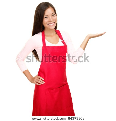 Small shop owner showing empty copy space in red apron. Woman smiling happy presenting with open hand palm. Friendly multiracial Asian Caucasian female model isolated on white background - stock photo