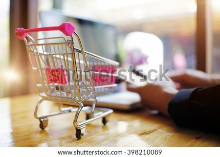 small shopping cart and a hand with credit card ,for shopping online concept. - stock photo
