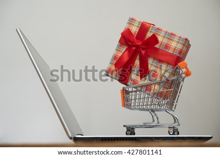 small Shopping cart stand on laptop with gift box isolated on white or gray background. red bow. present for customers - stock photo