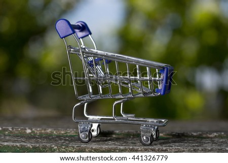 small shopping cart, studio picture on a wooden table - stock photo