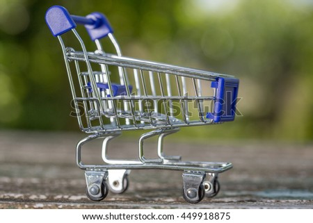 small shopping cart, studio picture on a wooden table