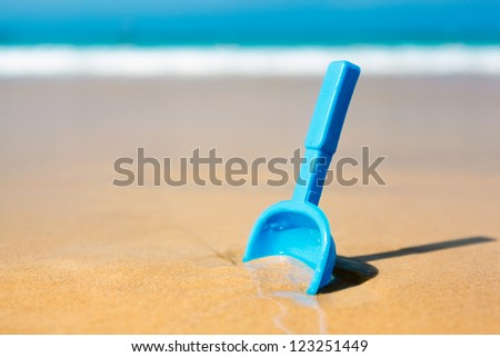 Small shovel in the sand on the beach - concept image - stock photo