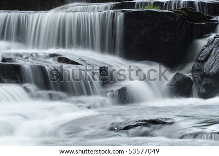 small silky smooth waterfall with flowing creek over rocks - stock photo