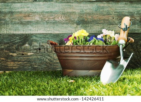 Small silver metal garden trowel propped up against a tub filled with colourful flowers in front of a rustic wooden garden shed with copyspace