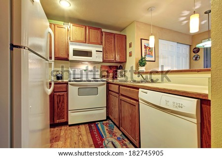 Small simple kitchen room with white  old appliances and wooden cabinets