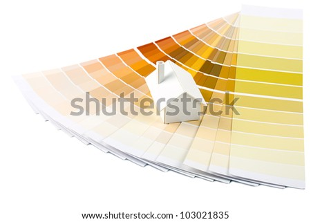 Small simple white model house on a color palette with different colors of spectrum. - stock photo