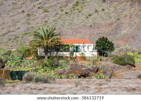 Small single house in near the village Vueltas on the headland of the Valle Gran Rey. The house, typical for the island La Gomera, is situated at the edge from the canyon who makes the valley famous - stock photo
