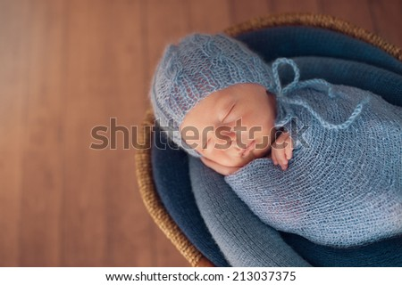 Small Sleeping Newborn Baby in Basket on Floor - stock photo