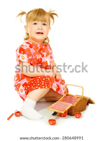 Small smiling baby in red dress with toy basket isolated - stock photo