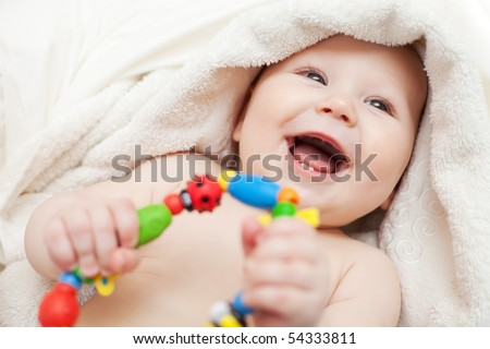 Small smiling baby with a toy