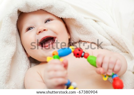 Small smiling baby with a toy - stock photo
