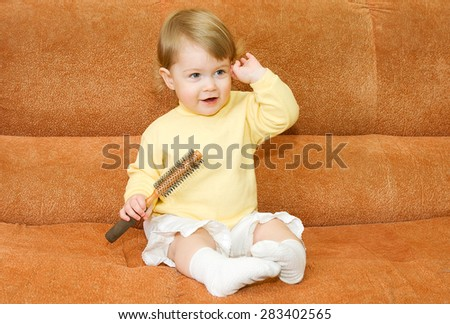 Small smiling baby with brush - stock photo
