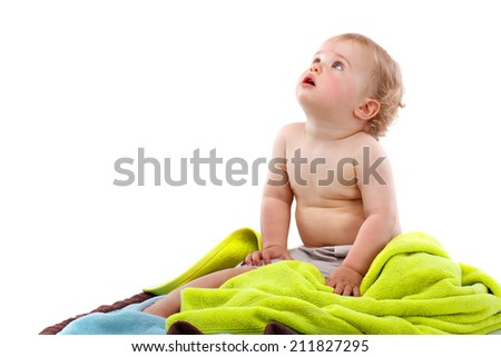 Small smiling blond curly boy sitting on colorful towels - stock photo