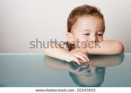 Small smiling boy sitting by a glass table - stock photo