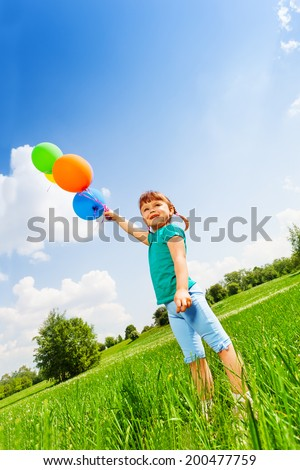 Small smiling girl with colorful balloons