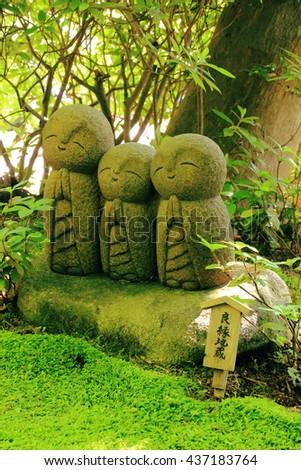 small smiling stone buddha monk statue stock photo