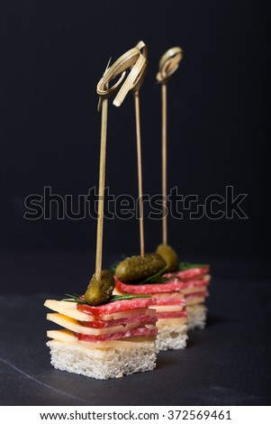 Small snacks canape with salami, cheese and pickle on skewer on a black slate plate. Shallow depth of field. - stock photo